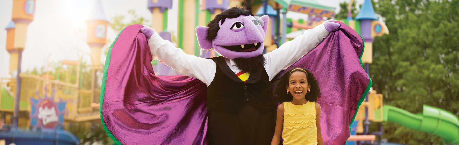 Count von Count raises cape behind a young girl at Sesame Place theme park