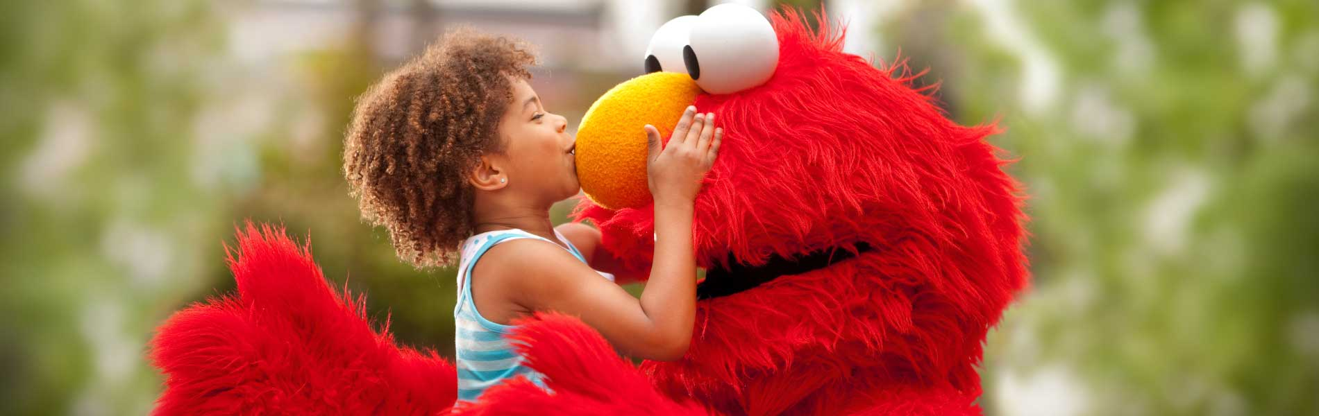 Elmo gets kissed on the nose by a young girl at Sesame Place theme park